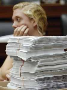 An intern for Waxman waits with stacks of paperwork in anticipation of a committee meeting to mark-up health care legislation on Capitol Hill in Washington