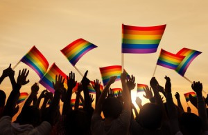 35337530 - silhouettes of people holding gay pride symbol flag