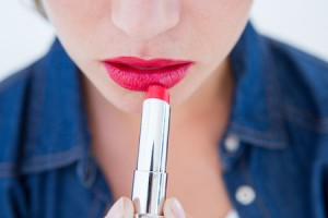 38311481 - woman putting red lipstick on white background