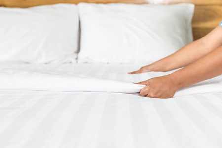 66219330 - close up hand set up white bed sheet in hotel room