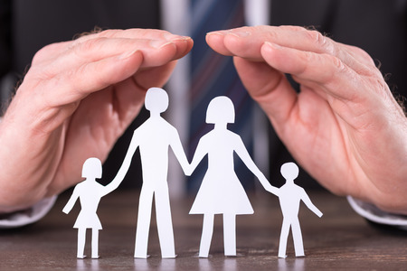 51688167 - concept of family insurance with hands protecting a family