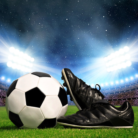 40322047 - soccer ball and shoes in grass soccer stadium with the dright lights
