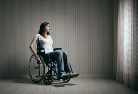 19753737 - sad woman sitting on wheelchair in empty room