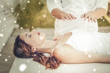 47306417 - snow against calm woman receiving reiki treatment