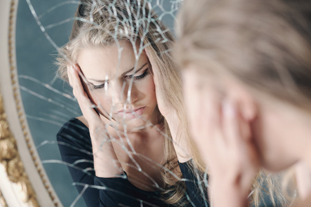 66120325 - girl with depression reflected in broken mirror